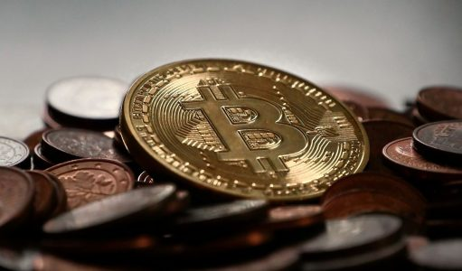 Golden bitcoin (BTC) in a pile of bronze fiat currency