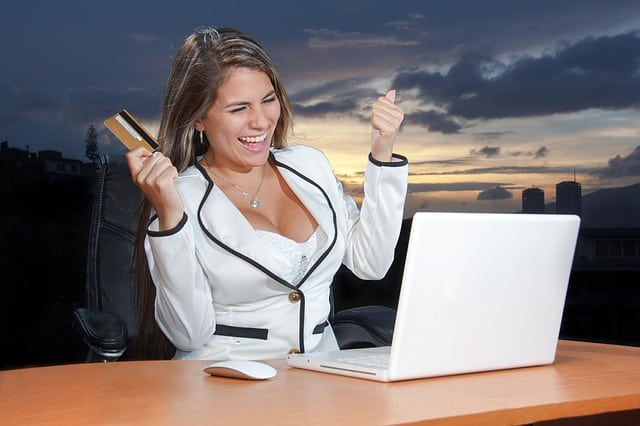 Unreasonably excited woman with a payment card in her hand sitting at a laptop